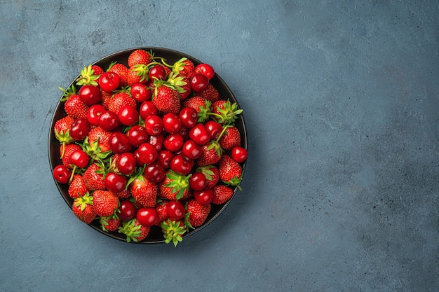 복사할 공간이 있는 진한 파란색 배경의 평평한 접시에 즙이 많은 체리와 딸기. 여름 딸기와 과일.