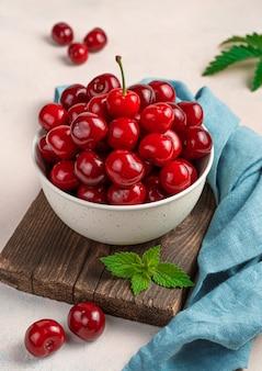 분홍색 배경에 있는 나무 판자에 있는 접시에 달콤한 체리. 클로즈업, 세로 보기입니다.