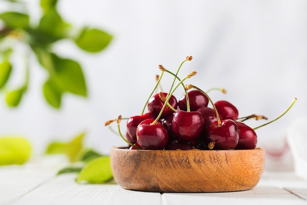 Сочные ягоды вишни в деревянной миске на деревянном столе