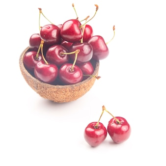 Juicy cherry berry in a bowl of coconut on a white background. fruits and vitamins. healthy food for breakfast. fruits of vegetation. fruit dessert