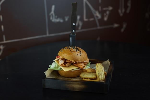Сочный куриный бекон с сыром хедер с красным луком с зеленью и соусом цезарь с куриным филе с запеченными дольками позолоченного картофеля на деревянной доске в ресторане. вкусный ужин