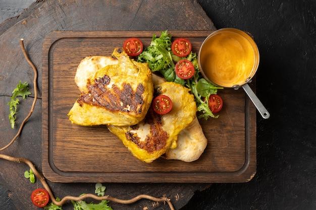 Сочная куриная грудка, обжаренная на шашлыке до румяной корочки с домашним соусом, помидорами черри и листьями салата.