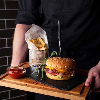 Juicy chicken burger  french fries on a wooden board.