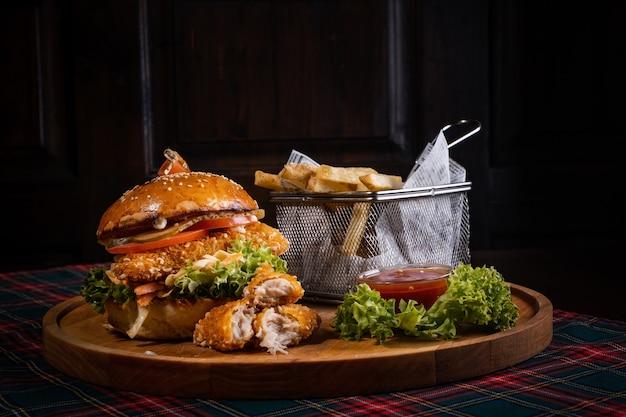 Hamburger di pollo succoso con lattuga fresca e patatine fritte croccanti su una tavola di legno