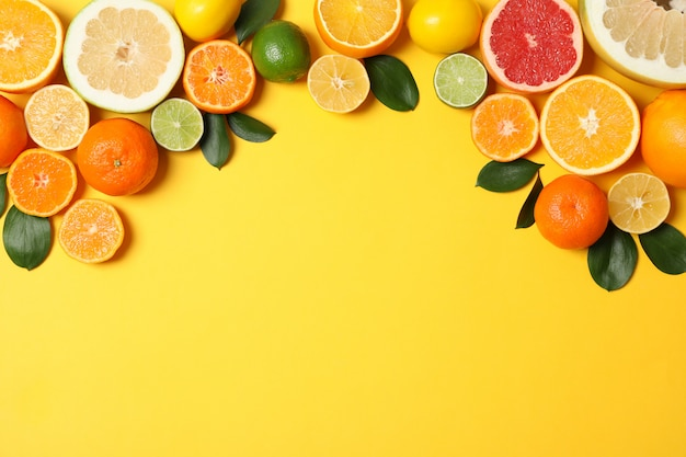 Juicy citrus fruits and leaves on yellow background, space for text