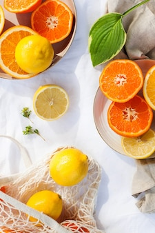 Juicy citrus fruits whole and cut on the tablecloth