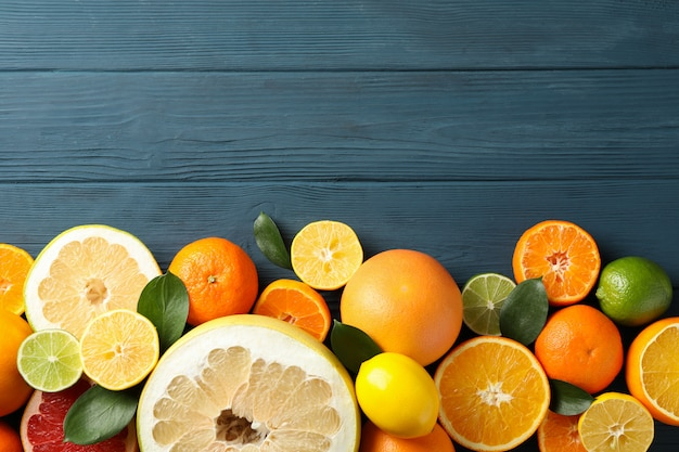 Juicy citrus fruits on wooden background, space for text