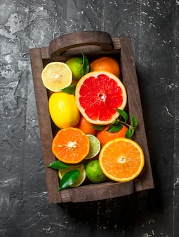 Juicy citrus in a wooden box. on black rustic table