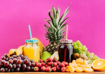 Juicy colorful fruits and juice mason jars against pink background