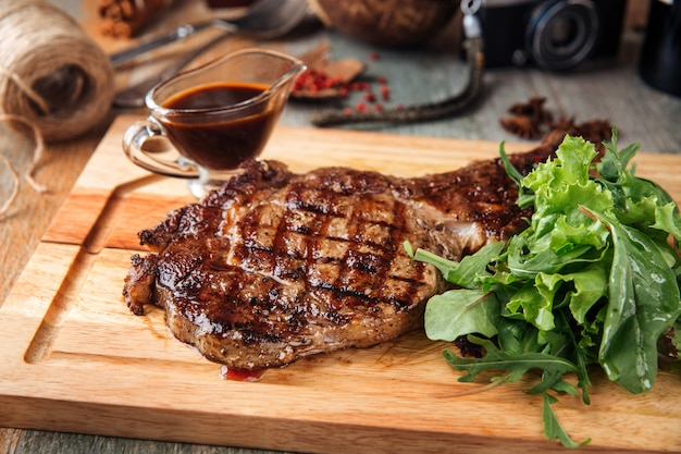 Juicy cooked cowboy steak with sauce and salad