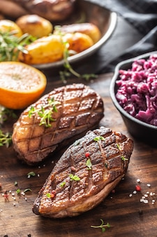Juicy cooked duck breasts with red cabbage, orange and potatoes on a wooden board.