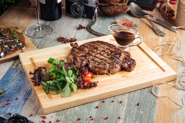 Juicy cooked ribeye steak with sauce and salad