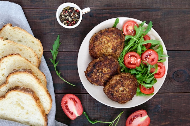 暗い木製のルッコラとトマトのサラダプレートにジューシーなカツレツ。