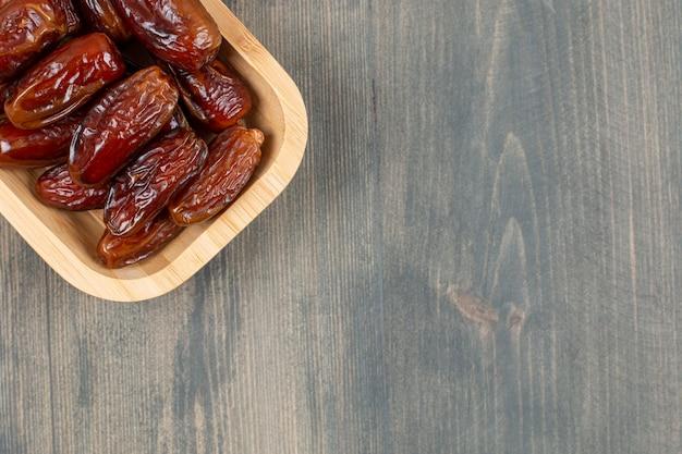 木製のテーブルの上の木製のプレートでジューシーな日付。高品質の写真