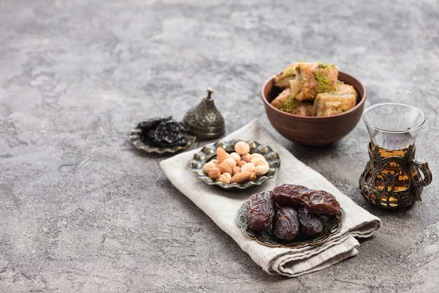 Juicy dates; nuts; herbal tea and baklava sweets in bowl on concrete textured backdrop