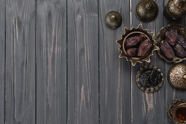 Juicy dates on turkish arabic metallic bowl on wooden plank