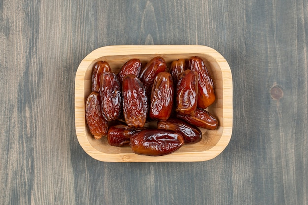 Juicy dates in a wooden plate on a wooden table . high quality photo