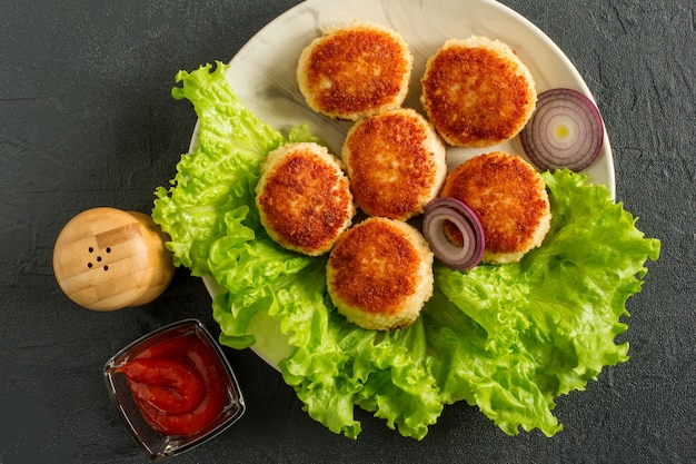 Сочные вкусные покрытые панировочными сухарями и жареными куриными котлетами на белой тарелке со специями и кетчупом на темном фоне, вид сверху.