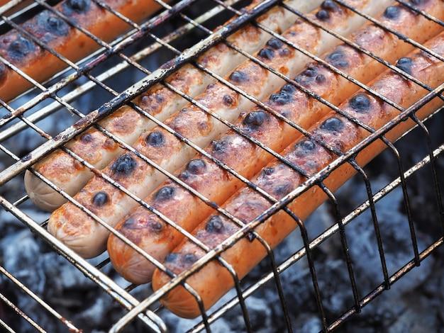 Сочные вкусные колбаски на гриле жарят в гриле на углях