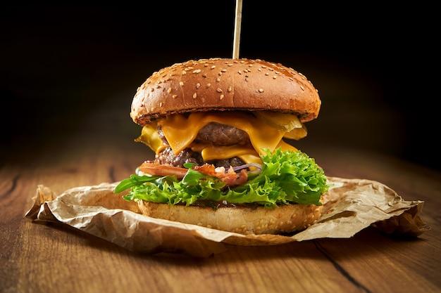 Сочный двойной бургер с говядиной, салатом, солеными огурцами, беконом и сыром чеддер, подается на пергаменте на деревянном столе