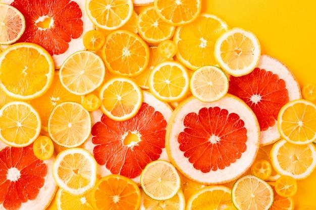 柑橘系の果物とジューシーな新鮮な明るい夏黄色背景、フラットレイアウト。