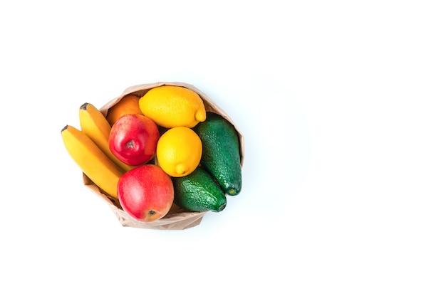 흰색 배경에 고립 된 크 라프 트 가방에 육즙 신선한 과일. 복사 공간이있는 상위 뷰. 건강한 식습관의 개념.