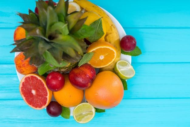 Сочная тарелка со свежими фруктами на синем деревянном фоне