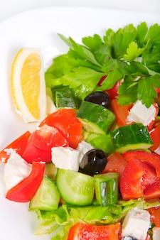Juicy fresh greek salad in white bowl