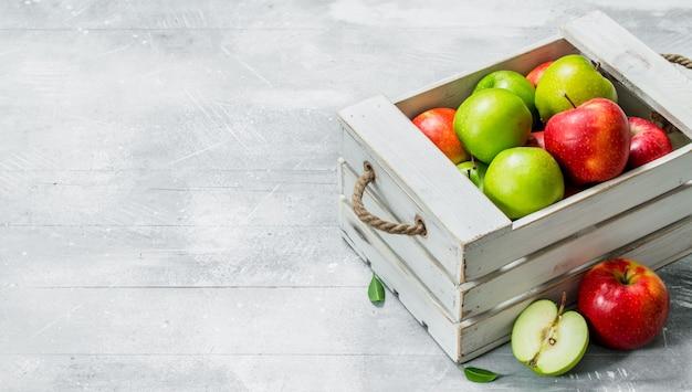 木製の箱にジューシーな新鮮な緑と赤のリンゴ。