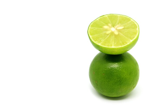 Juicy fresh lime in cross section put over the whole fruit isolated on white background