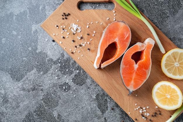 양파, 레몬, 천연 슬레이트 돌 테이블에 향신료와 나무 절단 보드에 육즙 신선한 연어 스테이크, 클로즈업. 맛있게 조리 된 연어 필레.