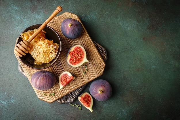 ジューシーな新鮮なイチジクの丸ごとフルーツと1つのカットイチジクと蜂蜜のボウルを木製のまな板のハニカムに入れます。上面図