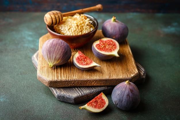 Сочные свежие цельные плоды инжира и один нарезанный инжир и миска меда в сотах на деревянной разделочной доске