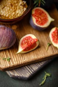 ジューシーな新鮮なイチジクの丸ごとの果物と木製のまな板のハニカムの1つのカットイチジクと蜂蜜のボウル