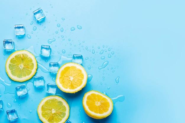 青い背景にジューシーな新鮮な黄色のカットレモンと角氷。上面図、フラットレイ。