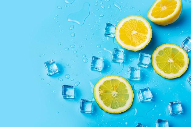 青い背景にジューシーな新鮮な黄色のレモンスライスと角氷。上面図、フラットレイ。
