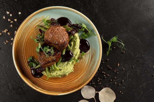 Juicy fried fillet mignon steak with asparagus bean puree and berry sauce.