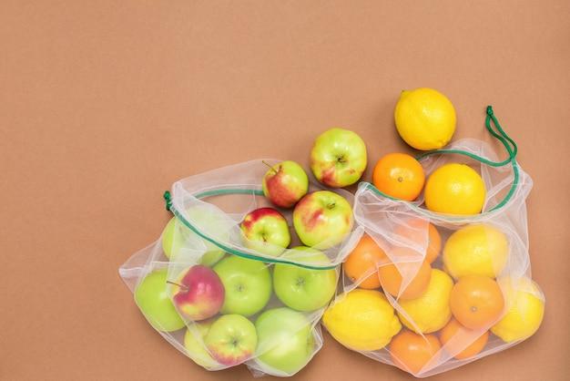 Сочные фрукты в экологически чистых сетчатых мешочках на коричневом фоне. без пластика, без отходов, многоразовое использование.
