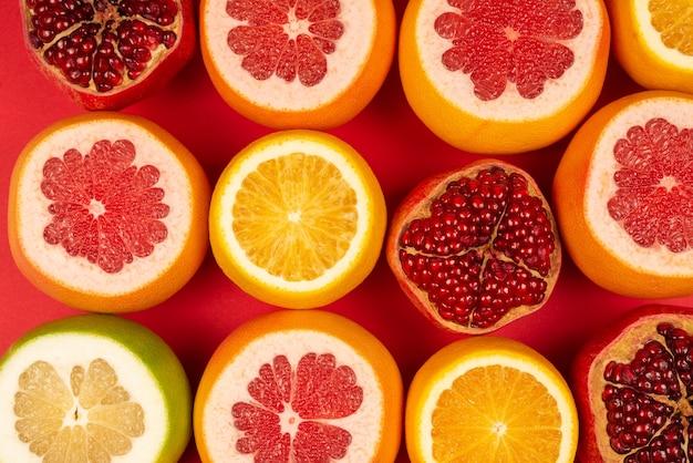 Сочный грейпфрут, апельсин, гранат, конфета цитрусовых на красном фоне.