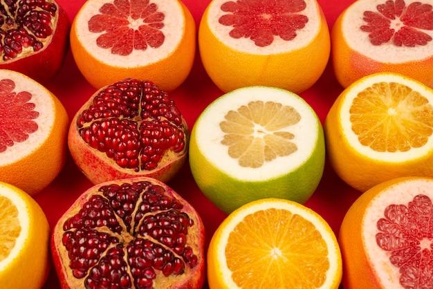 Сочный грейпфрут, апельсин, гранат, цитрусовые конфетки на красном фоне