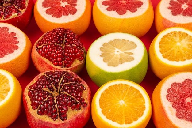 Сочный грейпфрут, апельсин, гранат, цитрусовый конфет на красном