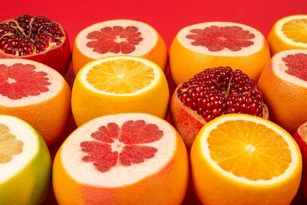 Juicy grapefruit, orange, pomegranate, citrus sweetie on red background.