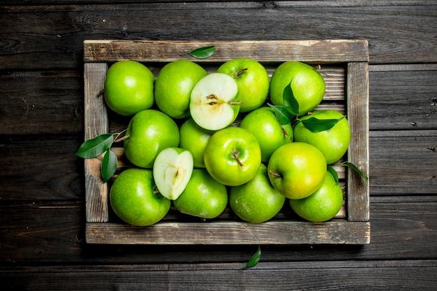 수 분이 많은 녹색 사과 나무 상자에 사과 조각. 어두운 나무 배경.