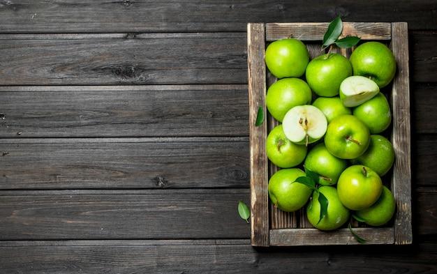 수 분이 많은 녹색 사과 나무 상자에 사과 조각.