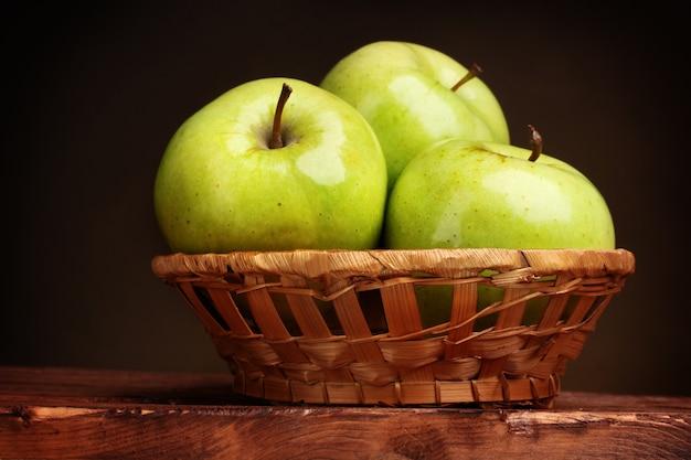 木製のテーブルの上のバスケットにジューシーな青リンゴ