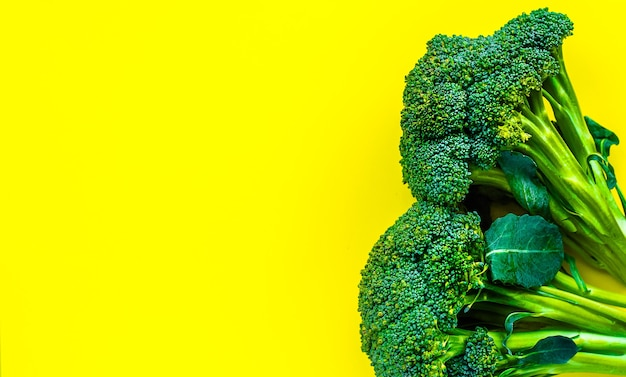 Juicy greens and broccoli on a yellow background place for inscription