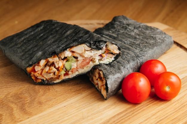야채와 향신료 고기와 함께 나무 보드에 맛있게 구운 검은 shawarma. 블랙 도너 케밥