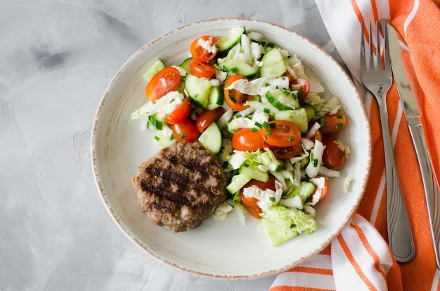 Juicy grilled cutlet with fresh vegetable salad on gray background.