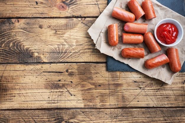 Сочные жареные половинки мясных колбас с томатным соусом и кетчупом на деревянном фоне. жир фаст-фуд. концепция нездоровой пищи. копировать пространство