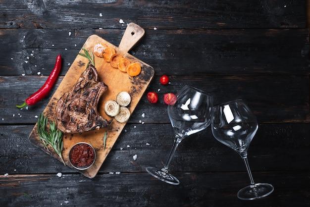古い木の上にワインとグラスのボトルとジューシーなグリルポークステーキ。ジューシーな食品の背景。